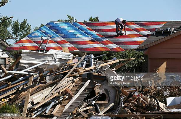 Artist Scott LoBaido of Staten Island New York paints an American Flag on the roof of a home damaged by a tornado June 2 2013 in Moore Oklahoma...