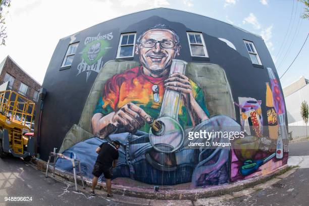 Artist Scott Marsh puts the finishing touches to a mural of Senator Richard Di Natale titled 'Legalize It' in the Sydney suburb of Newtown on April...