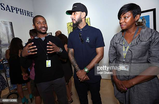 Artist Shawn Warren discusses his paintings with musician Swizz Beatz and Frances Guichard in the Bombay Sapphire Artisan Series Lounge at Scope art...