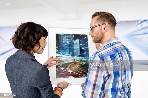 Künstler zeigen Galeriebesitzerin beim seine Arbeit