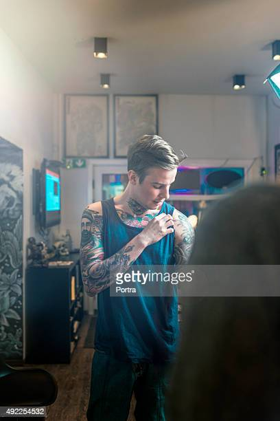 Artist showing tattoo on his arm to customer