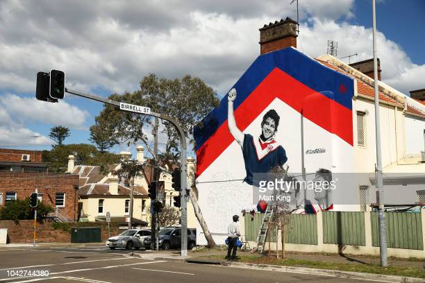 Artist Sid Tapia works on a mural that depicts former Sydney Roosters players Arthur Beetson Brad Fittler and Anthony Minichiello ahead of the the...