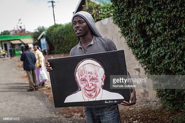 Artist Simon Kizito tries to sell his painting of Pope Francis in Nairobi's Kangemi slum on November 24 2015 in Kenya Pope Francis makes his first...