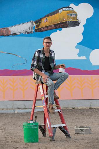Artist sitting on ladder near mural - gettyimageskorea