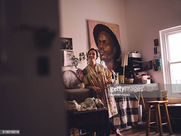 Artist smiling in bright studio with art equipment around her