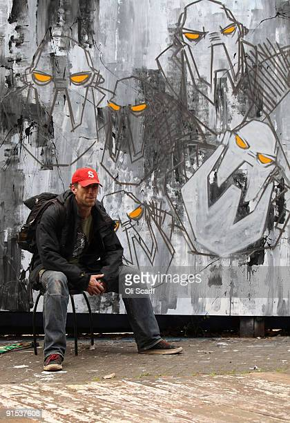 Artist 'Snub23' poses next to his partfinished artwork in the 'One Foot in the Grove' exhibition of street art by 'Mutate Britain' under the Westway...