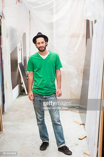 Artist standing in studio surrounded by canvasses.