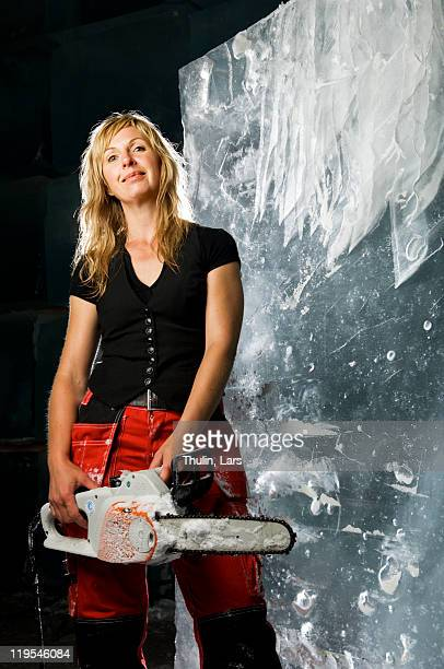 Artist standing with electric saw in front of ice block