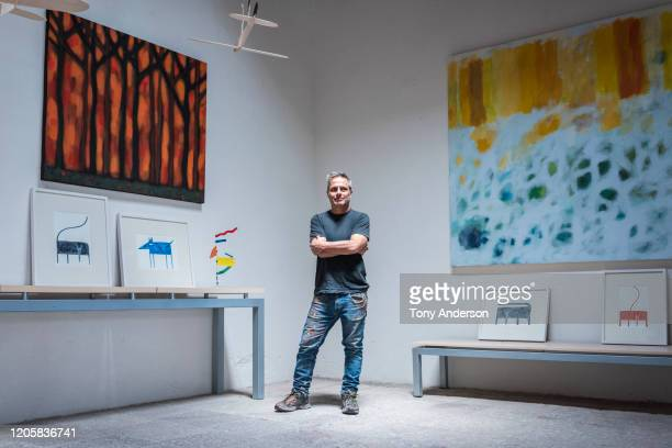 artist standing with his paintings in his studio - artist stock pictures, royalty-free photos & images