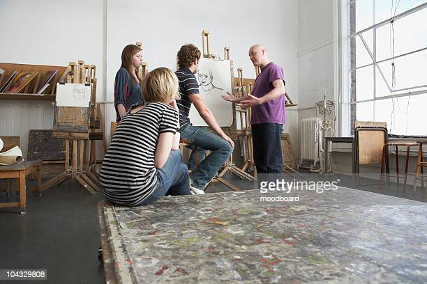 Artist talking to young artists in studio