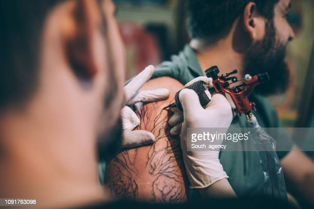 artist tattooing a man in studio - tattoo stock pictures, royalty-free photos & images