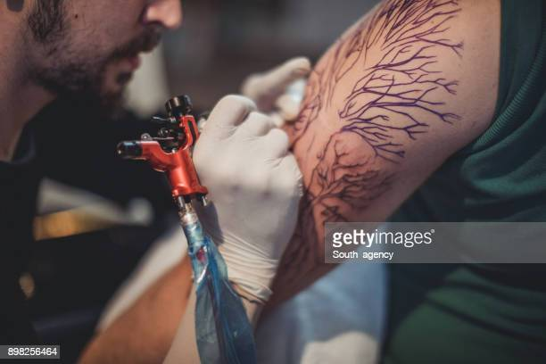 Artist tattooing a man's arm