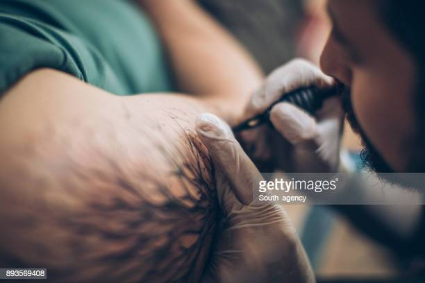 Artist tattooing arm