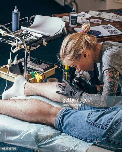 Artist tattooing design on mans leg at studio