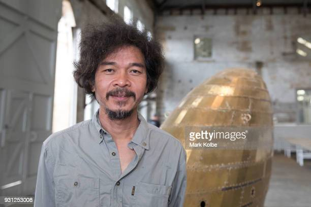 Artist Tawatchai Puntusawasdi poses with is artwork 'Super Moon 21' which is part of the 31st Biennale of Sydney at Cockatoo Island on March 13 2018...
