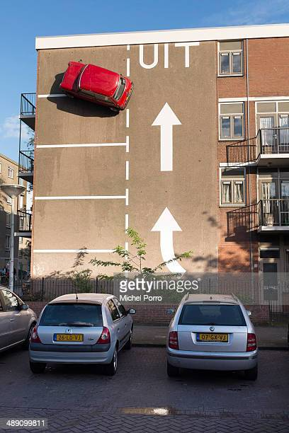 Artist Theo van Laar has designed a creative solution to solve his parking problem and installed his Mini high on a wall on May 09 2014 in The Hague...