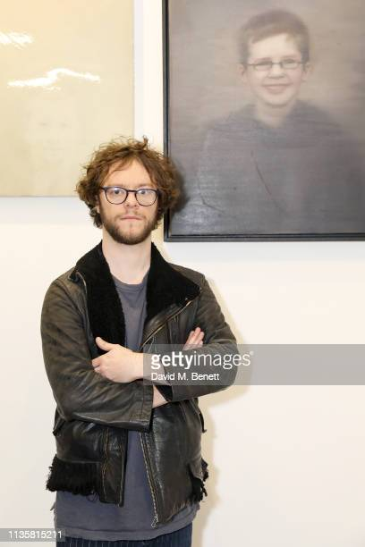 Artist Tim Gatenby poses with his portrait from the Unmissable25 exhibition during the private view of The Other Art Fair at The Old Truman Brewery...
