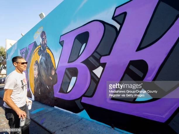 Artist Tyke looks over the mural of Kobe and Gianna Bryan he painted on the side of El Toro Bravo market on W 19th Street in Costa Mesa CA on Friday...