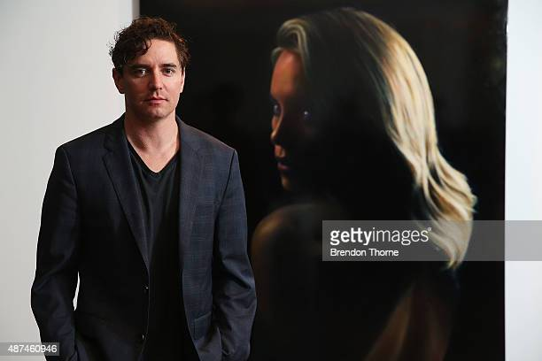 Artist, Vincent Fantauzzo poses in front of his portrait unveiling of Charlize Theron on September 10, 2015 in Sydney, Australia.