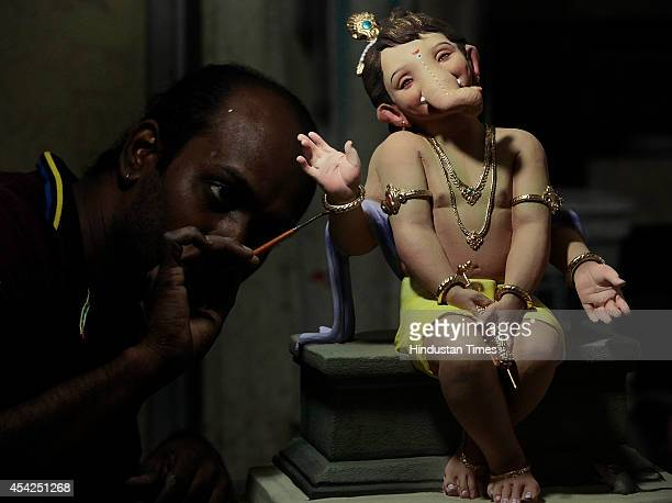 Artist Vishal Shinde giving finishing touches to Ganesha clay idol ahead of the forthcoming Ganesh Chaturthi festival at his workshop in Worli on...
