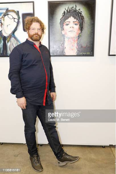Artist Will Teather poses with his portrait from the Unmissable25 exhibition during the private view of The Other Art Fair at The Old Truman Brewery...