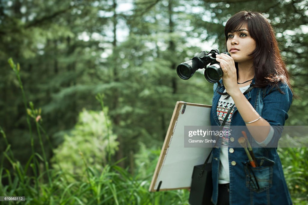 Artist with binocular, drawing board and art equipments searching subject. : Stock Photo