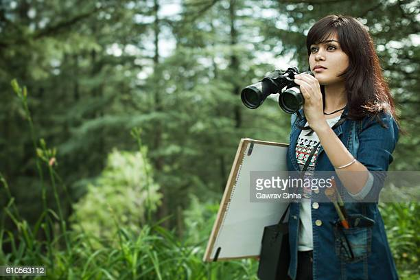 Artist with binocular, drawing board and art equipments searching subject.