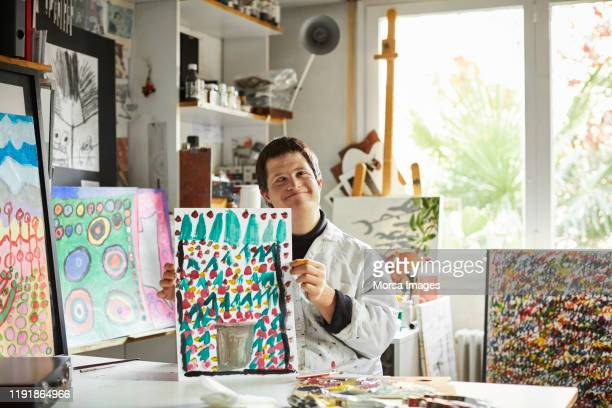 artist with down syndrome showing painting - intellectually disabled stock pictures, royalty-free photos & images