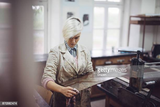 artist with dyed blond hair cleaning the graphics mould in her workshop - etching stock pictures, royalty-free photos & images