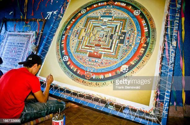 Artist working at a big Mandala