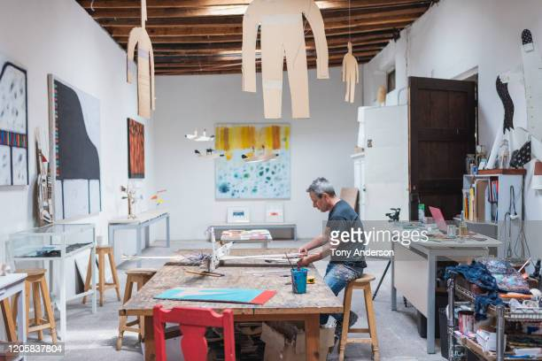 artist working in his studio - hanging stock pictures, royalty-free photos & images