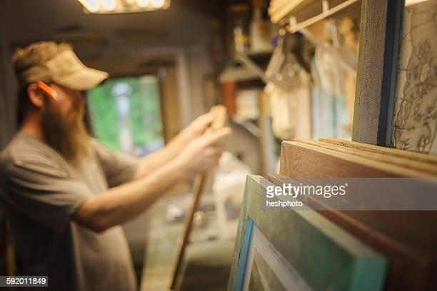 artist working in workshop, wooden frames in foreground - heshphoto stock-fotos und bilder
