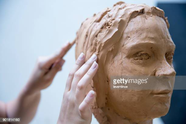 artist working on clay sculpture in art studio - sculpture stock pictures, royalty-free photos & images