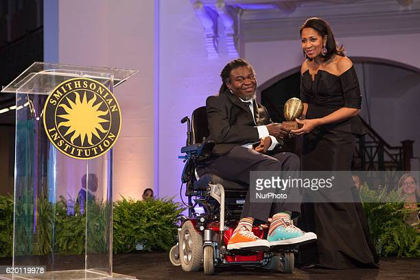 artist Yinka Shonibare accepts his African Art Award from Amelia Quist Ogunlesi at The Smithsonian National Museum of African Art's 1st annual...