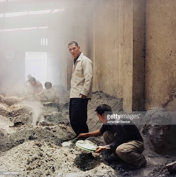 Artist Zhang Huan is photographed for Vanity Fair Magazine on May 10, 2007 with his assistants in his 'crematorium' of his studios in Shanghai,...