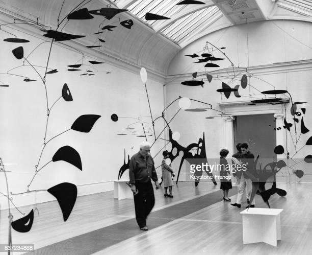 L'artiste Alexander Calder vérifie quelquesuns de ses mobiles lors d'une exposition de son oeuvre à la Tate Gallery le 3 juillet 1962 à Londres...