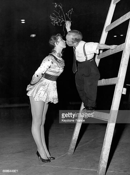 Artiste de cirque nain surnommé 'Little Tommy' embrassant une jolie danseuse sous une branche de gui à Londres RoyaumeUni le 18 décembre 1956