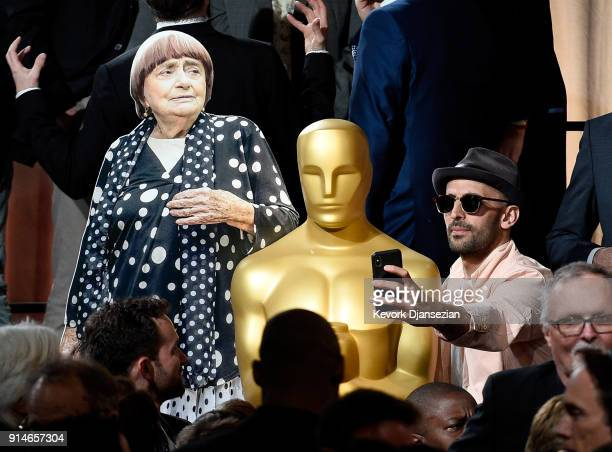 Artist/filmmaker JR takes a selfie with an Oscar statue and a cardboard cutout of collaborator Agnes Varda during the 90th Annual Academy Awards...