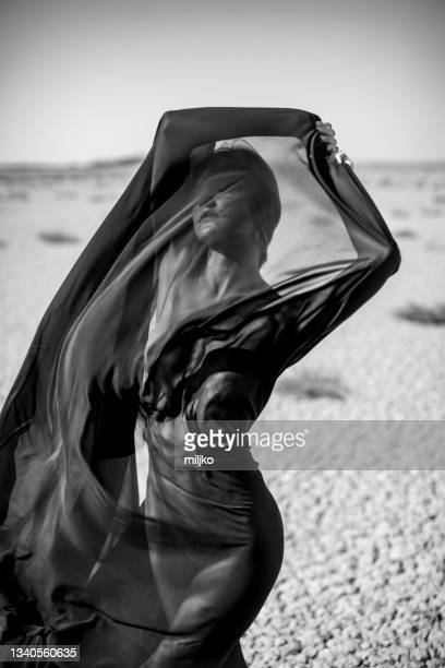 artistic abstract portrait of woman covered with black fabric in desert - sheer fabric stock pictures, royalty-free photos & images