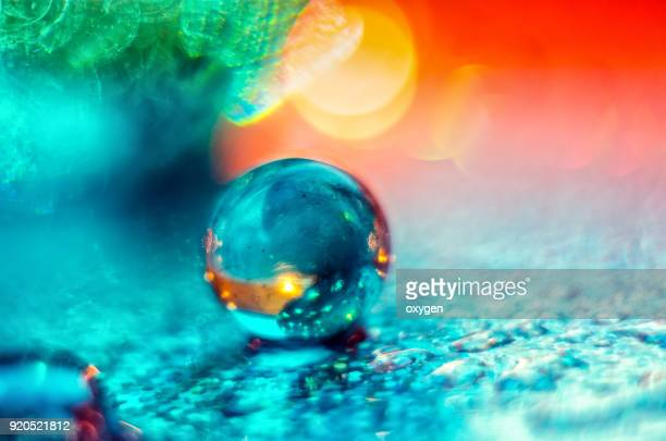 Artistic composition of blue and orange glass ball with water drop