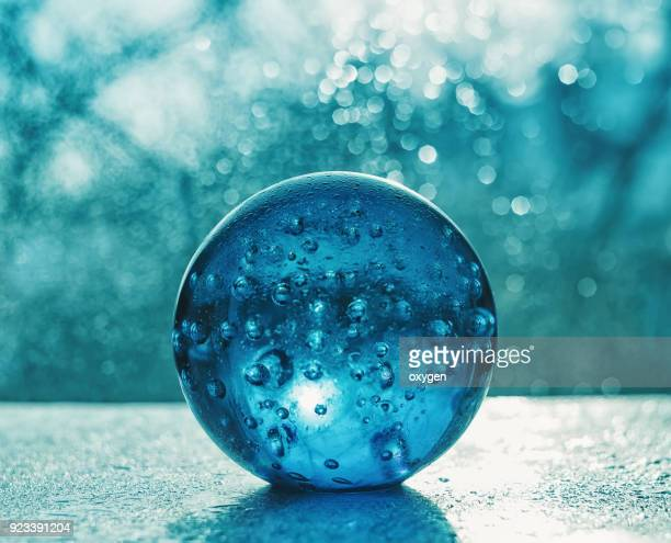 Artistic composition of blue glass ball with water drop