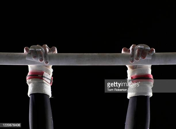 artistic gymnast mounting asymmetric bars - artistic gymnastics stock pictures, royalty-free photos & images