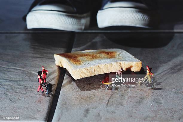 Artistic Image Of Figurines Cleaning Bread And Jam Fallen On Floor
