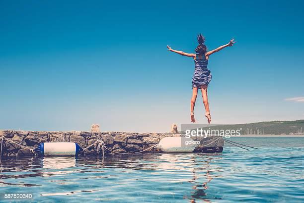 artistic teenage girl jumping high at croatian adria sea