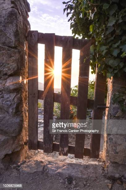 Artistic view of a summer sunset with sunbeams and lens flare through a wood gate in Corsica, France