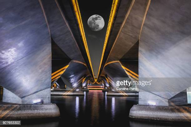 Artistic view of bridge with full moon.