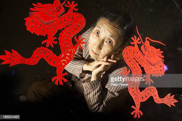 Portrait of 72year old Sun PeiLian with two of her paper cutout dragons for story about the older women network millennium art festival celebrating...