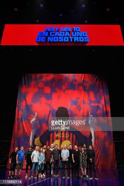 Artists and staff of the Canadian entertainment company Cirque du Soleil pose in front of a banner depicting Argentinian forward Lionel Messi during...