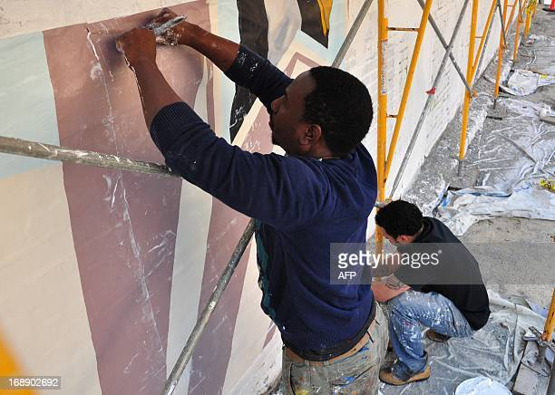 Artists apply panels for a mural on a wall in Philadelphia 30 April 2013 Philadelphia counts some 3800 murals across the city from historic downtown...