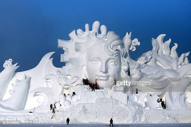 Artists carve the 103meterlong snow sculpture 'Long Song' for the 29th Harbin International Snow Sculpture Art Expo at Sun Island on December 13 2016...